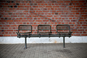 bench with three seats in front of a brick wall