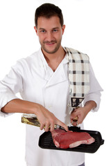 Young attractive caucasian male cook with, preparing steak