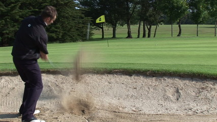Rear view of a golfer on the sand trying the eighth hole