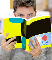 Male student in a library hiding his face behind a book
