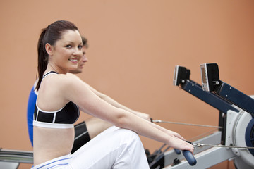 Happy woman with her boyfriend using a rower in a fitness centre