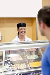 Joyful baker behind her display talking to customer