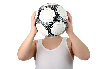 Unknown small boy holds soccer ball in front of his head isolate