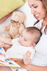 Portrait of joyful mother reading a book to her baby