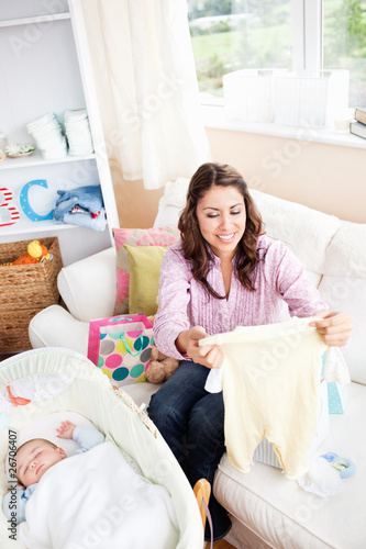 Joyful young mom holding a baby pyjamas sitting on sofa
