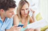 Focused couple calculating bills using a calculator at home