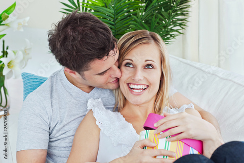 Handsome man kissing her girlfriend after giving her a present
