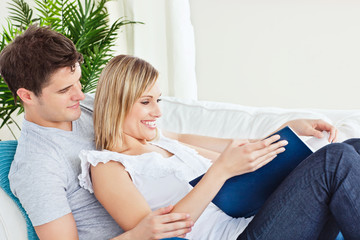 Cute couple browsing a book lying on the sofa