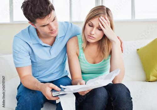Worried woman looking at bills with her boyfriend at home