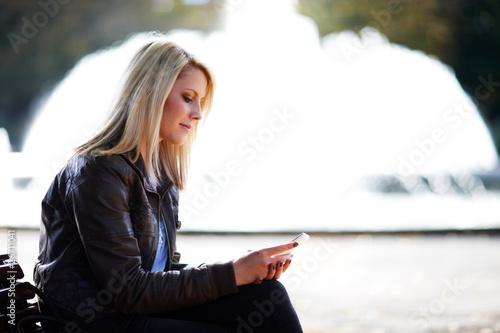 Leinwanddruck Bild Junge Frau mit Smartphone schreibt SMS