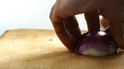Chef hand slicing onion on a board for cooking meal