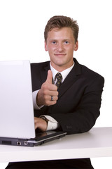 Businessman working on laptop and gesturing with thumbs up
