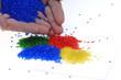 Farbiges Kunststoffgranulat mit Hand