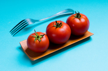 ripe tomatoes and plug on blue background