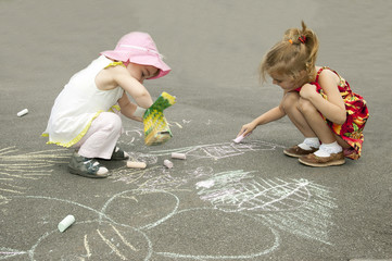 Children draw on asphalt.