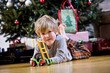 Little boy playing with toy by Christmas tree