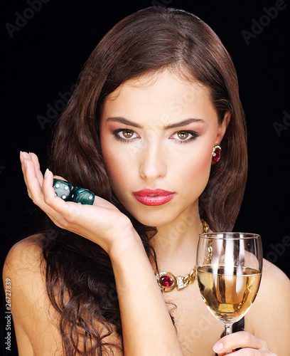 pretty young woman holding dices on black background