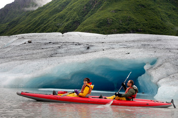 Happy young couple kayaking in Valdez glacial lake