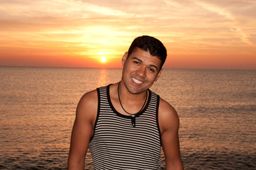 Young brazilian man siling at the beach at sunrise