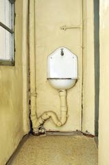 altes Waschbecken mit Wasserhan und Abflussrohr