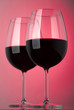 Two glasses of red wine on a pink background