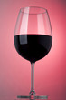 Glass of red wine on a pink background