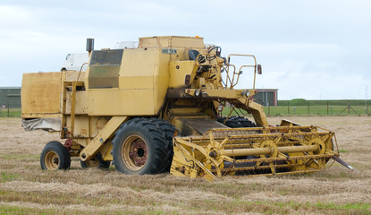 old combine harvester in field