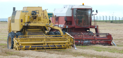 old and new combine harvesters in field