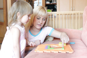 mother and daughter playing with puzzle at home