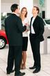 Paar bei Verkäufer im Autohaus