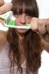 Зубная щетка и паста в руках девушки