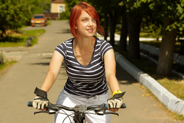 young adult smiling biker woman on mounting bike