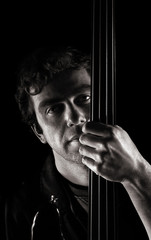 handsome musician  posing with fretless electric bass