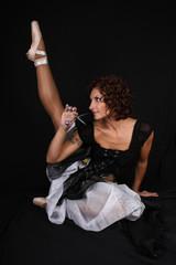 ballerina with scissors sitting over black background