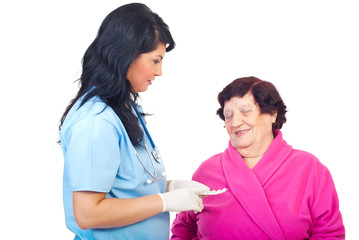 Doctor woman give pills to elderly woman