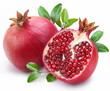 Leinwanddruck Bild - Juicy pomegranate and its half with leaves.
