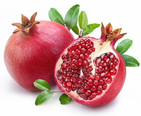 Juicy pomegranate and its half with leaves. © volff