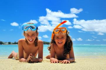 Fillettes en vacances, allongées sur le sable.