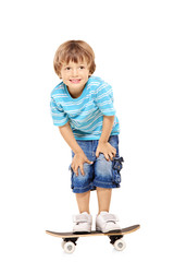 Full length portrait of an adorable young boy riding a skateboar