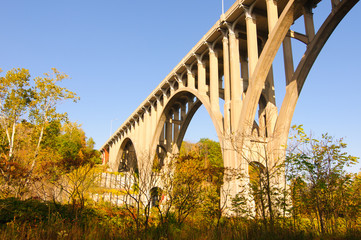 A high arch bridge spanning a valley in autumn