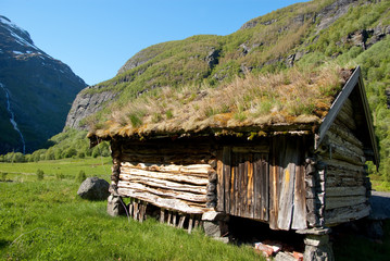 Old, wood cabin with grass on the roof in the Norwegian fjords.