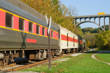 Scenic excursion train nearing a high arch bridge