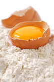 Broken egg with shells on flour, white backdrop