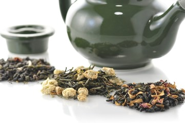 teapot and variety of loose tea with fruits and flowers