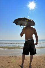 Homme avec un parapluie à la plage