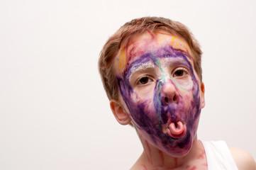 bambino con viso mascherato e linguaccia