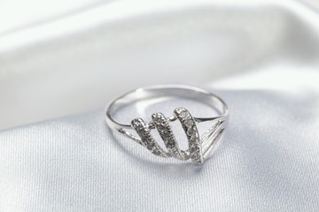 Jewelry, platinum or silver ring on white textile