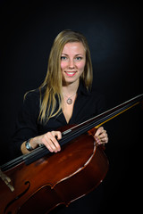 Portrait of young cellist smileing on black background