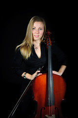 Young cellist standing and smileing on black background