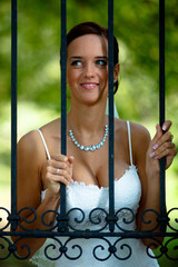 Bride portrait on a garden fence, looking and waiting